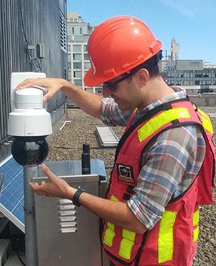 Multivista employee installing 24/7 live construction webcam on job site