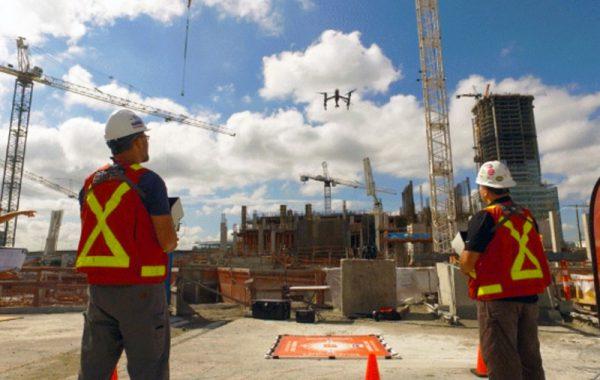 Multivista pilots flying construction drones/UAVs above construction site