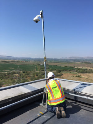 Multivista employee installing a 24/7 live-stream webcam on a client's construction site